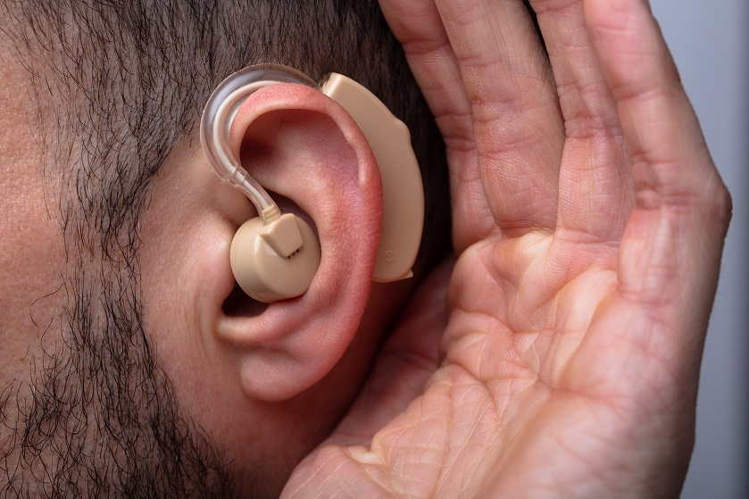 Close-up,Of,A,Man's,Hand,Inserting,Hearing,Aid,In,His